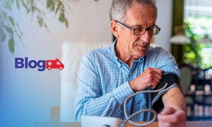 Homem idoso sentado em poltrona aferindo sua pressão com aparelho digital