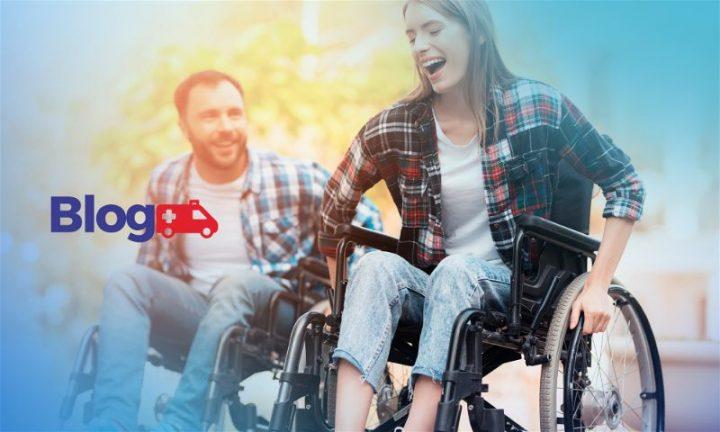Banner com mulher em primeiro plano e homem em segundo plano, ambos em cadeira de rodas sorridentes andando em local aberto