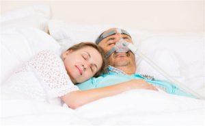 Homem idoso deitado na cama com aparelho de respiração com a esposa do lado