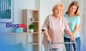 Banner com mulher idoso andando com ajuda de andador acompanhada por mulher, dentro de uma casa